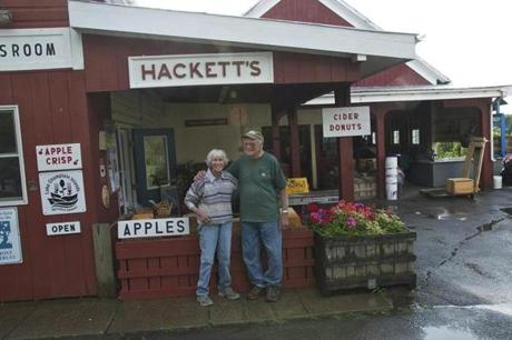 The rain let up, and Celia and Reynold Hackett step out to pose in front of their orchard stand in South Hero, a farm they took over in 1967, one that produces 47 apple varieties. Photo by Dirk Van Susteren.