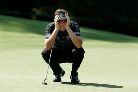 Englishman Ian Poulter gets a read on a putt on the fifth green.