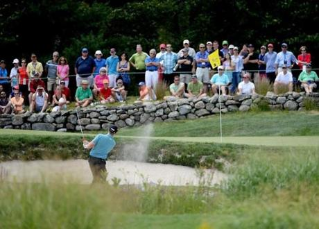 Hunter Mahan blasts from a greenside bunker on the third hole.