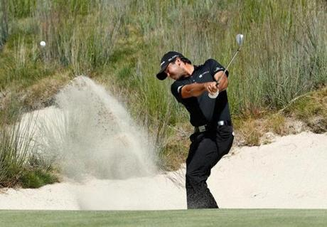Jason Day makes a splash in a bunker on No. 3.