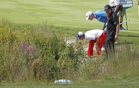 Ryo Ishikawa (white shirt) and Justin Hicks (blue shirt) help Phil Mickelson  look for his ball in a hazard on the second hole.