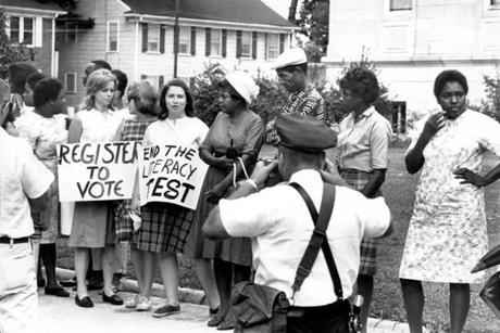 "A police officer took a photograph of a group, including Linda Wetmore (plaid dress, holding ""Register to Vote"" sign), standing outside of the Leflore County Courthouse in Greenwood, Miss., on July 16, 1964."