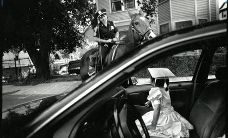 June 24 1993 / fromthearchive / Globe Staff photo by Suzanne Kreiter / Officer Robin DeMarco was one of the last mounted beat police officers who patroled a combination businss and residential neighborhood in Uphams Corner. She encountered 5 year old Rosyana Cardoso who was just returning from her preschool graduation exercises in a dress made for the occasion by her mother. The officer's graduation gift to the child was a ride on the horse.