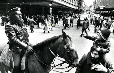 December 13 1977 / fromthearchive / Globe Staff photo by Stan Grossfeld / Tom Gemelli Jr. and his dad Tom Sr. stopped their Christmas shopping to look at Boston Police office Columbus Jennette and his horse at Downtown Crossing.