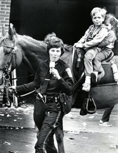 May 14 1978 / fromthearchive / Globe Staff photo by Stan Grossfeld / Boston Police Office Marie Donahue ate a popsicle as Jay and Beth DeDominici rode on her horse at the District 11 Open House.