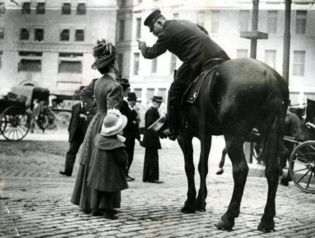 May 2 1910 / fromthearchive / Globe Staff photo by Joseph Dixon / The mounted police officer directed a lady and her child in Post Office Square.