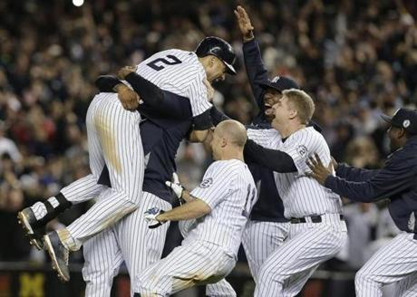 Jeter was mobbed by his teammates after driving in the winning run. (AP Photo/Julie Jacobson)