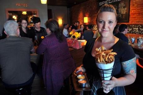 Mariah Pisha-Duffly holds the Portland restaurant's signature fries cooked in duck fat.