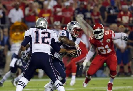Tom Brady handed the ball off to Shane Vereen in the first quarter.  (Barry Chin/Globe Staff)