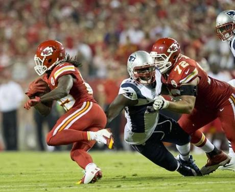 Chandler Jones was pulled down by Kansas City Chiefs tackle Eric Fisher,  which allowed Jamaal Charles to run for a big gain during second quarter. (Matthew J. Lee/Globe staff)