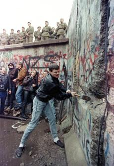 A demonstrator pounds away the Berlin Wall as East Berlin border guards look on from above the Brandenburg Gate in this November 11, 1989 file photo. In Berlin in 1987, former U.S. President Ronald Reagan challenged Soviet leader Mikhail Gorbachev to