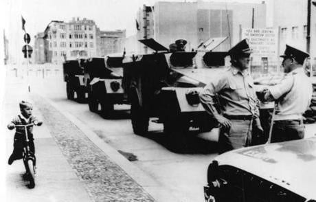 August 25 1962 / UPI Telephoto / WITHOUT PASSPORT - Little scooter-riding West Berliner whizzes past convoy of Soviet armored personnel carriers at Checkpoint Charlie in Berlin as British officer (right) and American officer discuss appropriate escort. berlinwall