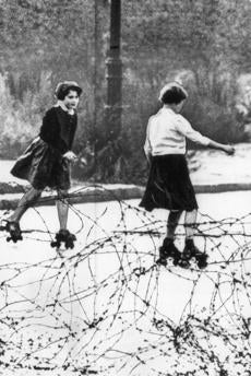August 15 1961 / UPI Telephoto / BERLIN. Two young girls roller skate on empty East Berlin street behind barbed wire barricade near the border of the American sector. As the East Germans tightened their stranglehold on East Berlin, scores of anti-communists were reported arrested. The flow of refugees, which had run as high as 2,000 in a single day last week before the border closing, was trimmed 8/15 to about 50 who eluded the border guards. berlinwall