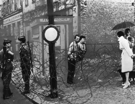 August 15 1961 / AP Wirephoto - BARBED WIRE NO BARRIER TO CONVERSATION - A West German couple, under umbrella, engage an East German couple in conversation over barbed wire along the border between East and West Berlin today near Dresdner Strasse. At left, two East German soldiers hold their own conversation. berlinwall