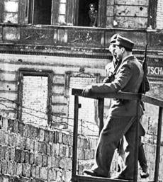 April 21 1962 / AP Wirephoto / A WATCH FROM THE WINDOW - An East German policeman keeps watch from an open window on two West Berlin policemen manning a post along the communist wall at Bernauer Strasse in Berlin today. Earlier the West Berlin and East German police exchanged gunfire and tear gas grenades in this area in an incident touched off by western holiday visitors taking a look at the wall. On communist side of the wall windows in buildings have been walled up leaving only a few open for police posts. berlinwall