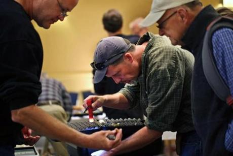 Marlborough, MA 10/12/14 Jonathan Burnham, center, Maine, examines marbles for sale by Kevin Gray, left, Ellington, CT. Ellington is showing a marble to Skip Palmieri, Pawcatuck, CT, right. Story is about the Northeast Marbles Meet convention, one of the largest and oldest marbles-collectors shows in the nation.