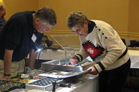 Marlborough, MA 10/12/14 Nancy Zeloski, Moultonborough, NH, right, shows Robert Block, left, photos of her marble collection. Story is about the Northeast Marbles Meet convention, one of the largest and oldest marbles-collectors shows in the nation.