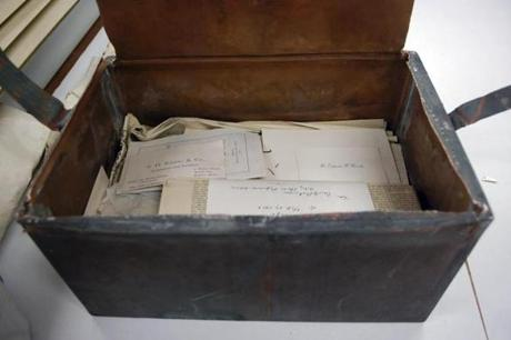 In this photo released Wednesday, Oct. 15, 2014 by the Bostonian Society, items are stacked inside a shoebox-sized 1901 time capsule in Boston. The capsule contained letters, photographs, newspaper clippings and the book