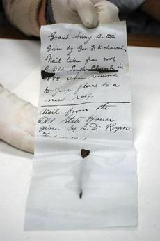 In this photo provided Wednesday, Oct. 15, 2014 by the Bostonian Society, a nail from Old South Church and a nail from the Old State House are displayed after they were taken from a 1901 time capsule in Boston. The 113-year-old, shoebox-sized time capsule was removed Oct. 9, 2014, from the head of a lion statue where it had long sat atop the Old State House, one of Boston's most famous landmarks. (AP Photo/Bostonian Society)
