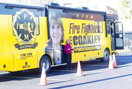 10:02 am - 10/25/14 - Dorchester, MA - PHOTO ESSAY - State Attorney General and Democratic candidate for Governor Martha Coakley spotted a bus with her face on it as she left a campaign event at the International Brotherhood of Electrical Workers (IBEW) Local 103 in Dorchester, MA on Saturday October 25, 2014. She ran to it and wanted her picture taken with it. One day on the campaign trail with Democratic candidate for Massachusetts Governor, State Attorney General Martha Coakley. Item: photo essays. Dina Rudick/Globe Staff.