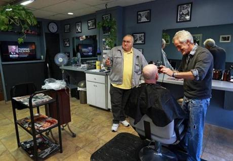 10/29/14: Boston, MA: John Cammarata (left), and Gino Colafella (working on a customer) are pictured in their North End barber shop on Hanover Street where the late Boston Mayor Thomas Menino used to get his hair cut. A television at left shows news coverage of the story. (Globe Staff Photo/Jim Davis) section: metro topic: menino