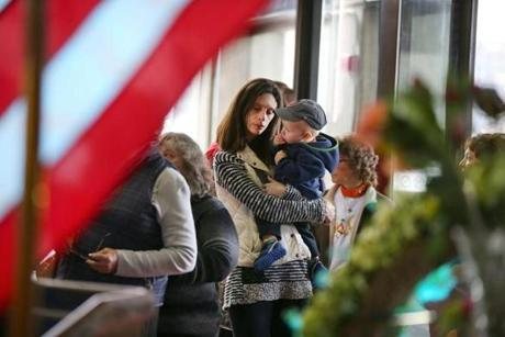 Boston10/31/2014- People waited in line to sign a condolence book in the lobby of Boston City Hall a day after the death of the former Boston mayor Thomas Menino. Amy DeLong waited to sign the book as she holds her son, Kyle, 13 months.
