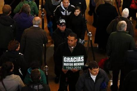 A man held a sign thanking Menino as he waited in line to pay his respects.
