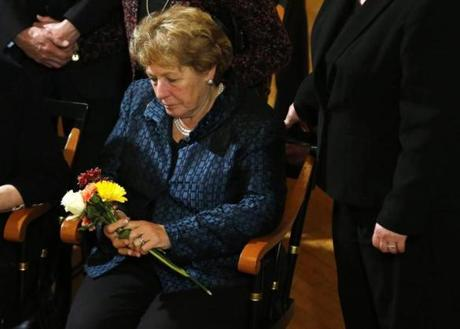 Angela Menino holds a bouquet of flowers brought to her by members of the public as former Mayor Thomas Menino lies in state inside Faneuil Hall.