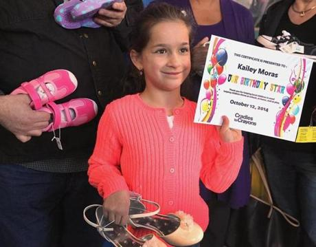 Boston, MA 111914 Kailey Moras (cq),8, of Methuen showed off a certification of appreciation from Cradles to Crayons in Brighton, Wednesday, November 19 2014. In lieu of presents for her birthday in October, Moras (cq) asked for shoe donations for children who cannot afford them. She collected 432 pair of shoes which she presented to Cradles to Crayons, an organization that provides children from birth through age 12 with essential items they need to thrive. (Wendy Maeda/Globe Staff) section: Metro slug: 20shoes reporter: