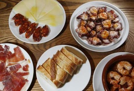 Top Row: Chorizo con Manchego (house-made sausage with cheese) sits beside Pulpo a la Gallega (Galacian octopus) along with Bottom Row: Jamon i berico, bread and Gambas ajillo (shrimp in garlic oil) on a table at Pintxo Pincho Tapas Bar in Woburn, Massachusetts January 16, 2014. (Jessica Rinaldi For The Boston Globe) 011115BOTNFood