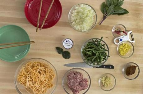 14apron - Ingredients for Blue Apron�s Curry Noodles with Pork & Long Beans dinner: clockwise, from top left, Thai basil, bird�s eye chili, ginger, yellow curry paste, garlic, ground pork, thickKaffir lime leaf, Chicken demi-glace, onions, Chinese long beans. (Jodi Bosin for The Boston Globe)