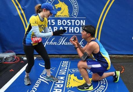 Boston-04/20/15- The Boston Marathon finish line. Mayor Marty Walsh's chief of staff Daniel Koh proposes to his fiancee Amy Sennett on the finish line after they both finished together. Walsh held the ring. Boston Globe staff photo by John Tlumacki (sports)