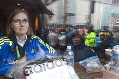 4/20/2015 - Boston, MA - Boylston Street - Dawn Mullis, cq, of Plano, TX, stayed warm in Starbucks as she waited for her husband to near the finish line. When he ran in 2011, he proposed immediately after finishing the race. Spectators lined the Boylston Street in Boston, near the finish of the 119th Boston Marathon on Monday, April 20, 2015. Topic: Race coverage. Photo by Dina Rudick/Globe Staff.