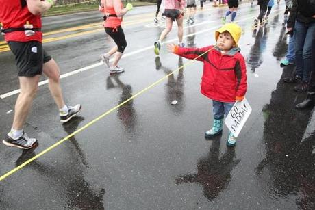 Newton, MA., 04/20/15, Three year old Santiago Winter of Belmont, waits for his father and high-fives other runners. Runners leave Wellesley and head into Newton for the 119th running of the Boston Marathon, Suzanne Kreiter/The Boston Globe