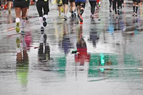 Newton, MA., 04/20/15, Runners are reflected in the slick pavement as they leave Wellesley and head into Newton for the 119th running of the Boston Marathon, Suzanne Kreiter/The Boston Globe