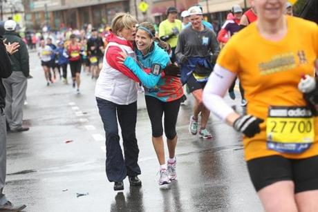 Newton, MA., 04/20/15, Running her sixteenth marathon, Kelli Hesseltine of Westford and running for Dana Farber, is greeted by her sister Patti Rocco of Gilford, NH. Runners leave Wellesley and head into Newton for the 119th running of the Boston Marathon, Suzanne Kreiter/The Boston Globe