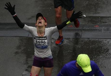 Boston, Massachusetts -- 4/20/2015-- Chandler Rainey reacts after crossing the Boston Marathon Finish Line in Boston, Massachusetts April 20, 2015. Jessica Rinaldi/Globe Staff Topic: Reporter: