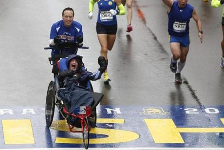 Boston, Massachusetts -- 4/20/2015-- Bryan Lyons pushes Rick Holt across the Boston Marathon Finish Line in Boston, Massachusetts April 20, 2015. Jessica Rinaldi/Globe Staff Topic: Reporter: