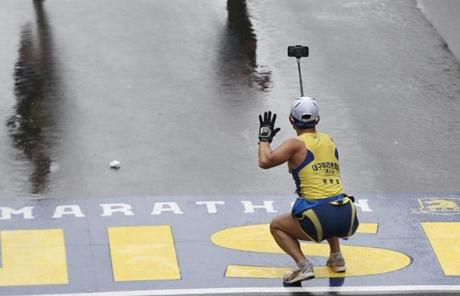 Boston, Massachusetts -- 4/20/2015-- A runner bends down to take a selfie as he crosses the Boston Marathon Finish Line in Boston, Massachusetts April 20, 2015. Jessica Rinaldi/Globe Staff Topic: Reporter: