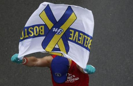 Boston, Massachusetts -- 4/20/2015-- A runner carries a flag that reads Believe in Boston as he crosses the Boston Marathon Finish Line in Boston, Massachusetts April 20, 2015. Jessica Rinaldi/Globe Staff Topic: Reporter: