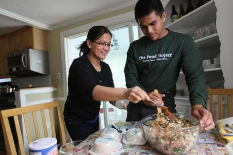 Gaurav Dangol mixes meat mixture while his mom, Krishna Maharjan, adds spices to make momos, meat and vegetable dumplings from Nepal.