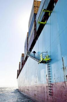 After being dropped off by a pilot boat, harbor pilot Scott MacNeil, 48, climbs a ladder to board the container ship Maersk Kalamata and guide it into the port of Boston.