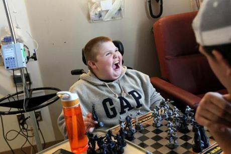 Austin plays chess while receiving an IV earlier this year.