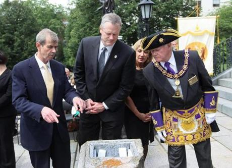 June, 17, 2015 -BOSTON, MA- From left, Secretary of the Commonweath William Francis Galvin, Gov. Charlie Baker, Lt Gov Karyn Polito and Grand Master of the Grand Lodge of Masons Harvey Waugh peek into the crevice that will hold the time capsule when it was revealed during ceremony at the Statehouse steps. (Boston Globe staff photo: Joanne Rathe topic: 18timecapsule reporter: josh miller section: metro)
