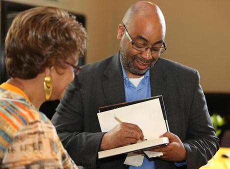 Adrian Miller autographs his book on soul food for Carole Copeland of Lakeville.
