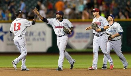 Pawtucket Red Sox's Jackie Bradley Jr., second from right, of the International League high-fives Indianapolis Indians' Alen Hanson after the team defeated the Pacific Coast League 4-3 during the Triple-A All-Star baseball game, Wednesday, July 15, 2105, in Papillion, Neb. (Megan Farmer/The Omaha-World-Herald via AP)