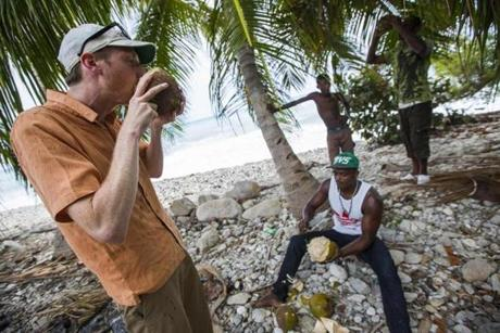 Hervens Nicolas (right) shared coconuts with Nathan Eckstrom in Marigot, Haiti, during his visit to student Alexandrine Theodore's hometown.