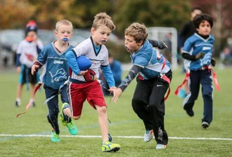Children were playing all sorts of sports on a recent Sunday in Lexington. Ansley Gallagher (left) runs the ball past Brendan Schwartz during a flag football game at Lincoln Park.
