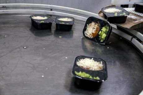 These packaged Boston School lunch is dumped off of a conveyor belt at the Whitsons Culinary Group headquarters in Islandia, New York, Oct. 19, 2015. (Johnny Milano for The Boston Globe)