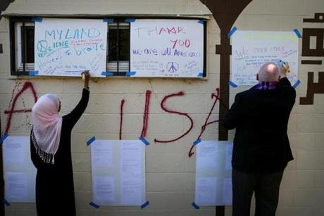 A member of the Islamic Center of Burlington and Michael O'Brien, (right) Interim Pastor at Presbyterian Church in Burlington, wrote positive messages on the wall of the building.